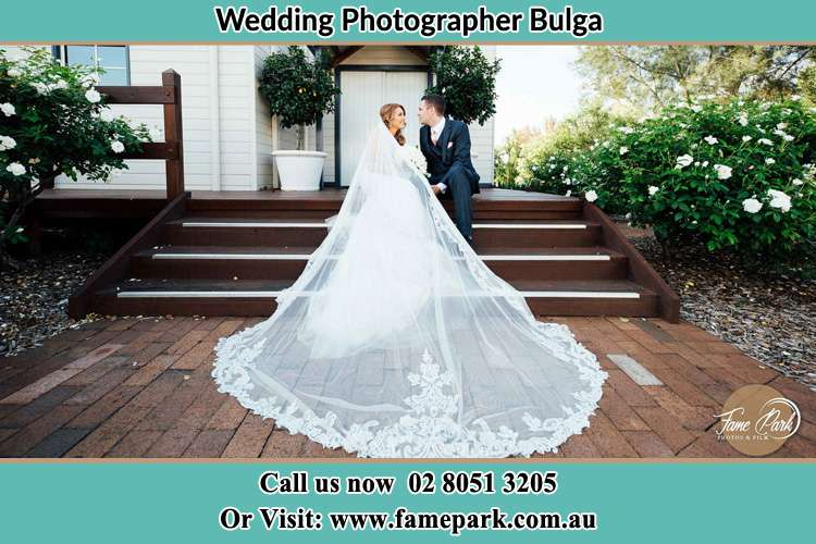 Photo of the Bride and the Groom looking each other while sitting at the staircase Bulga NSW 2330