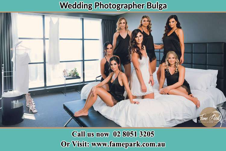 Photo of the Bride and the bridesmaids wearing lingerie on bed Bulga NSW 2330