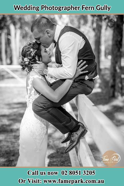 Photo of the Groom sitting on the fence while kissing the Bride on the forehead Fern Gully NSW 2330