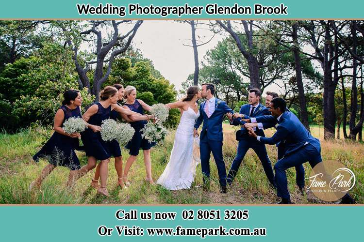 Photo of the Bride and the Groom kissing while teasing by the entourage Glendon Brook NSW 2330
