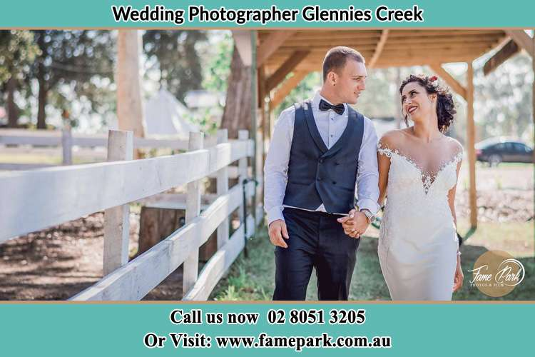 Photo of the Bride and the Groom holding hands while walking Glennies Creek NSW 2330