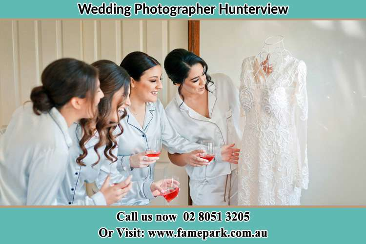 Photo of the Bride and the bridesmaids checking the wedding gown Hunterview NSW 2330