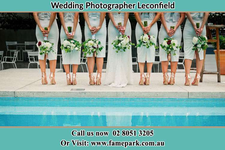 Behind photo of the Bride and the bridesmaids holding flowers near the pool Leconfield NSW 2335