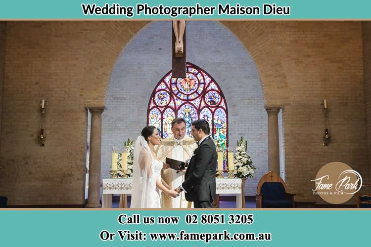 Photo of the Bride and Groom at the Altar with the Priest Maison Dieu NSW 2330