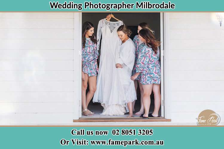 Photo of the Bride and the bridesmaids checking at wedding gown at the front door Milbrodale NSW 2330