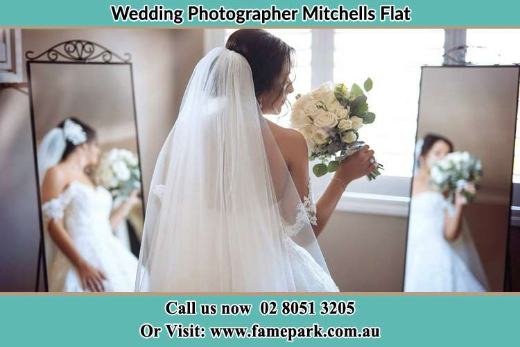 Photo of the Bride holding flower at the front of the mirrors Mitchells Flat NSW 2330