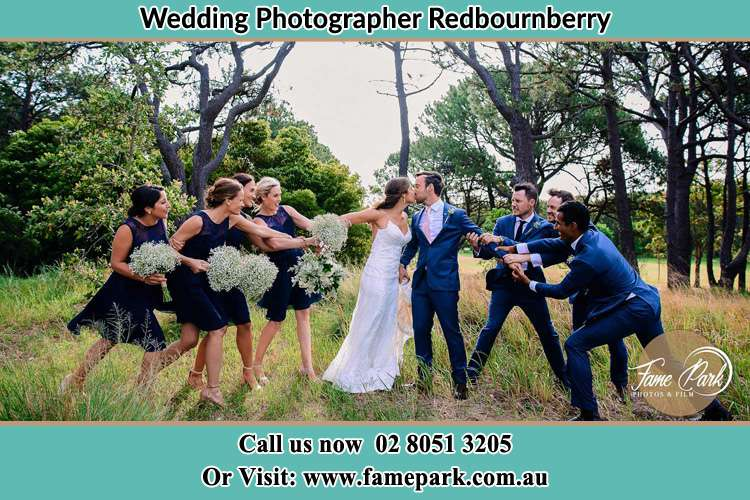 Photo of the Bride and the Groom kissing while teasing by the entourage Redbournberry NSW 2330