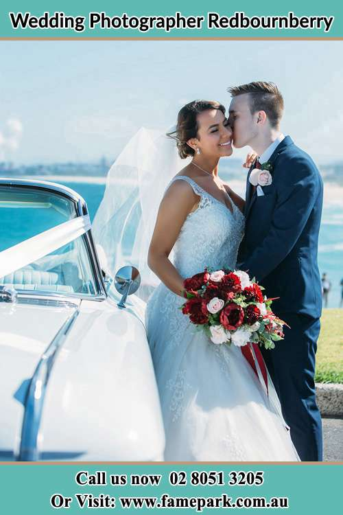 Photo of the Groom kiss the Bride besides the bridal car Redbournberry NSW 2330