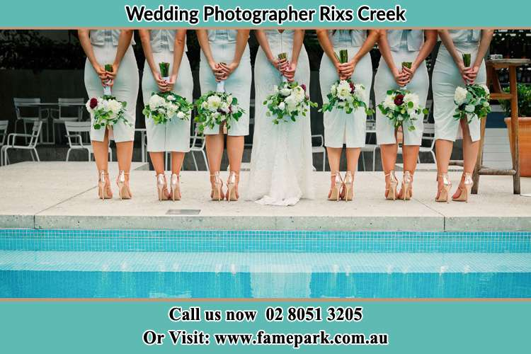 Behind photo of the Bride and the bridesmaids holding flowers near the pool Rixs Creek NSW 2330