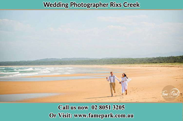 Photo of the Groom and the Bride walking at the sea shore Rixs Creek NSW 2330