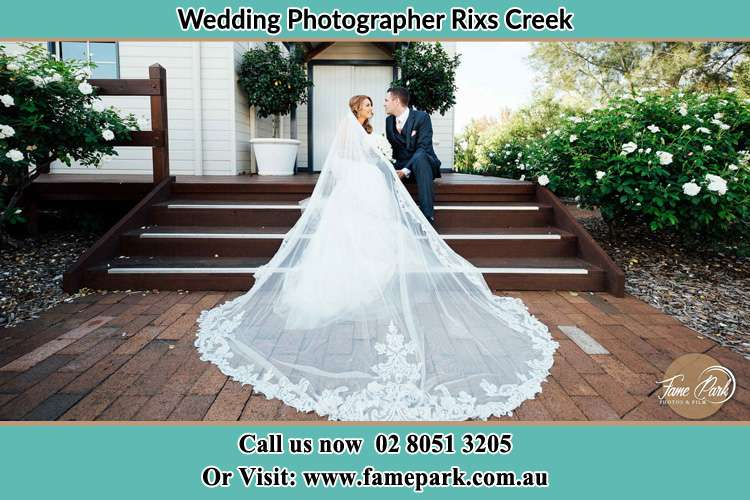 Photo of the Bride and the Groom looking each other while sitting at the staircase Rixs Creek NSW 2330