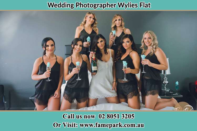 Photo of the Bride and the bridesmaids wearing lingerie and holding glass of wine on bed Wylies Flat NSW 2330